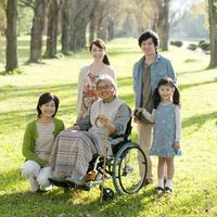 車椅子のシニア男性を囲む3世代家族