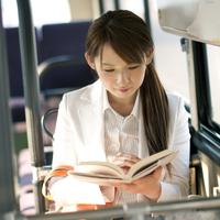 バスの中で本を読むビジネスウーマン
