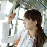 バスの中のつり革を持つビジネスウーマン