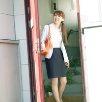 玄関の扉を開けるビジネスウーマン