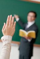 授業をする男性教師と手をあげた手元