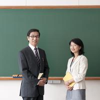 黒板の前に立つ男性教師と女性教師