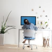 パソコンの前に座るビジネスウーマンの後姿
