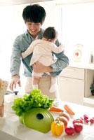 赤ちゃんを抱き料理をする父親