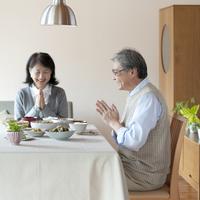 食事を前に手を合わせるシニア夫婦