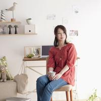 椅子に座りコーヒーカップを持つ女性