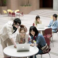 ノートパソコンの画面を見る留学生と女子大生