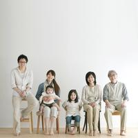 椅子に座り微笑む3世代家族