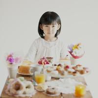 たくさんのお菓子を前に微笑む女の子