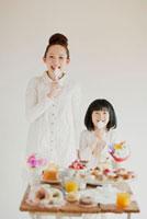 たくさんのお菓子とスプーンを持ち微笑む親子