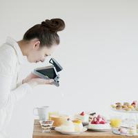 たくさんのお菓子の写真を撮る女性