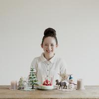 テーブルの上に並ぶクリスマスグッズと女性