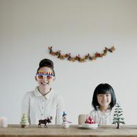 テーブルの上に並ぶクリスマスグッズと親子 20027008621| 写真素材・ストックフォト・画像・イラスト素材|アマナイメージズ