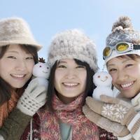 雪だるまを持ち微笑む3人の女性