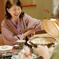旅館で土鍋のふたを開けるシニア女性