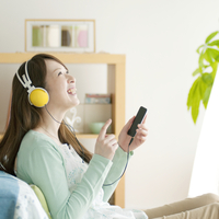 ヘッドホンを付け音楽を聴く女性