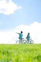 草原で自転車を押すカップルの後姿