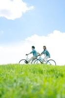 草原で自転車に乗るカップル 20027008946| 写真素材・ストックフォト・画像・イラスト素材|アマナイメージズ