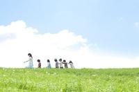 草原を歩く先生と小学生