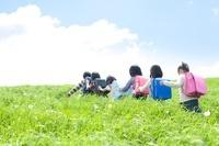草原を歩く小学生の後姿