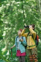 山道で双眼鏡を覗く女性