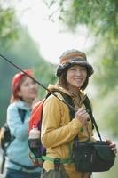 釣り竿を持ち微笑む女性