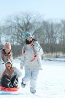 ソリで遊ぶ3人の女性