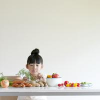 テーブルの上に並ぶ野菜を見る女の子