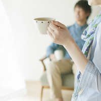 コーヒーカップを持つ女性の手元