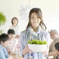 食事をする家族とサラダを持ち微笑む母親