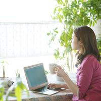 コーヒーを飲みながらパソコン操作をする女性 20027009478| 写真素材・ストックフォト・画像・イラスト素材|アマナイメージズ