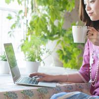 コーヒーを飲みながらパソコン操作をする女性