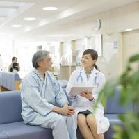 病院のロビーで女医と話をする患者