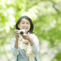 カメラを持ち微笑むシニア女性