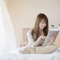ベッドに座りタブレットPCを操作する女性