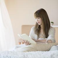 ベッドに座り本を読む女性