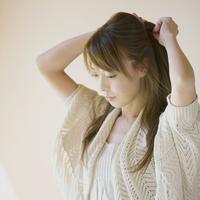 髪を束ねる女性の横顔