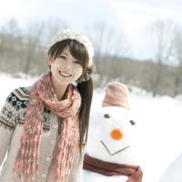 雪だるまの前で微笑む女性