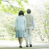 新緑の中を歩くシニア夫婦の後姿