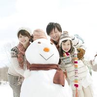 雪だるまの周りで微笑む家族