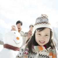 雪だるまの前で微笑む女の子
