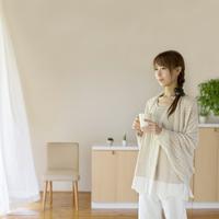 コーヒーカップを持ちリラックスをする女性