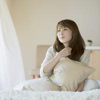 ベッドに座りリラックスをする女性
