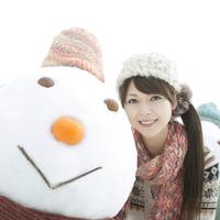 雪だるまの横で微笑む女性