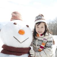 雪だるまの横で微笑む女の子