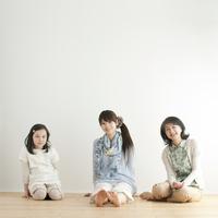 床に座り微笑む3世代家族
