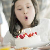 ケーキのろうそくの火を吹き消す女の子