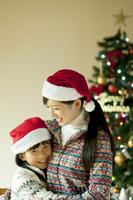 クリスマスツリーの前で抱き合う親子