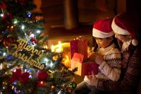 暖炉の前でクリスマスプレゼントを持つ親子