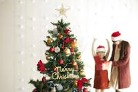 クリスマスツリーの後ろでプレゼントを開ける親子